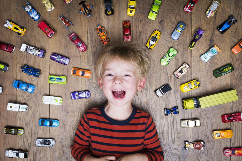 車のおもちゃを並べて喜ぶ子供