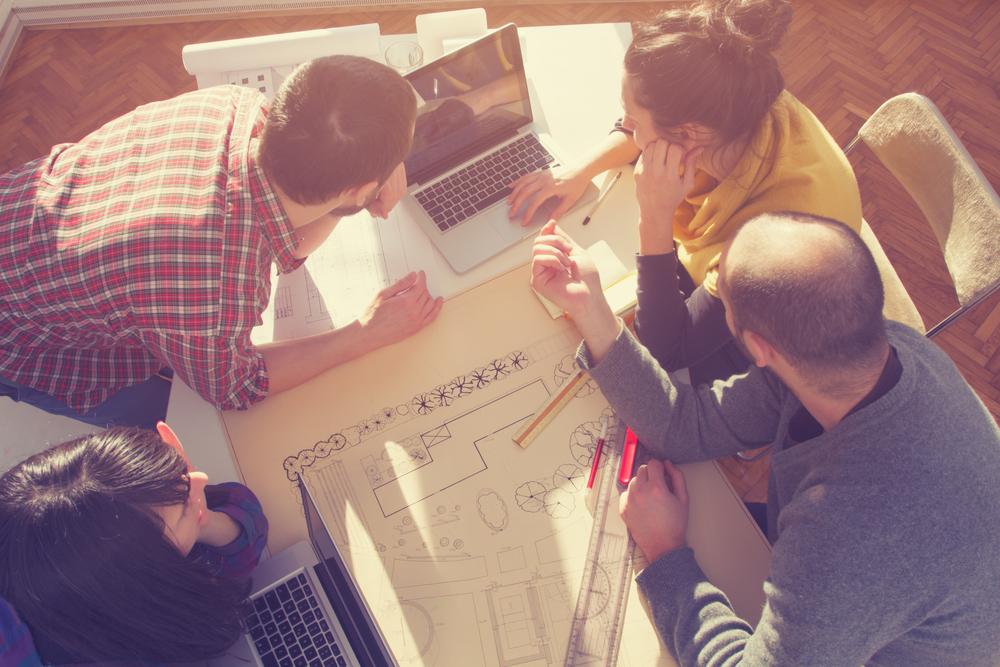 設計図を開きながら会議をする人々