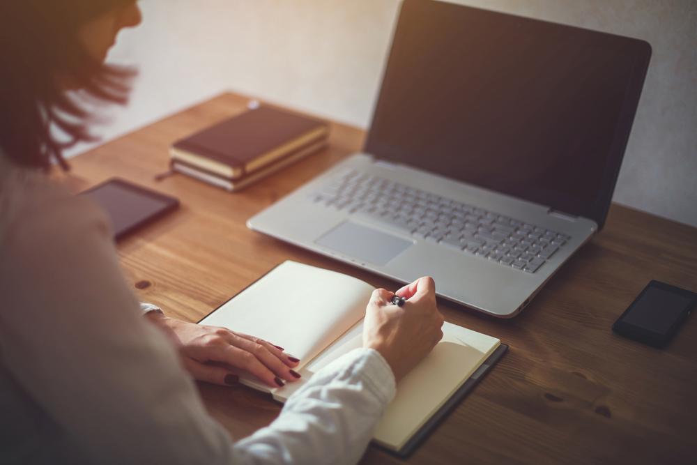 ノートパソコンを開きながらノートにメモを書く女性