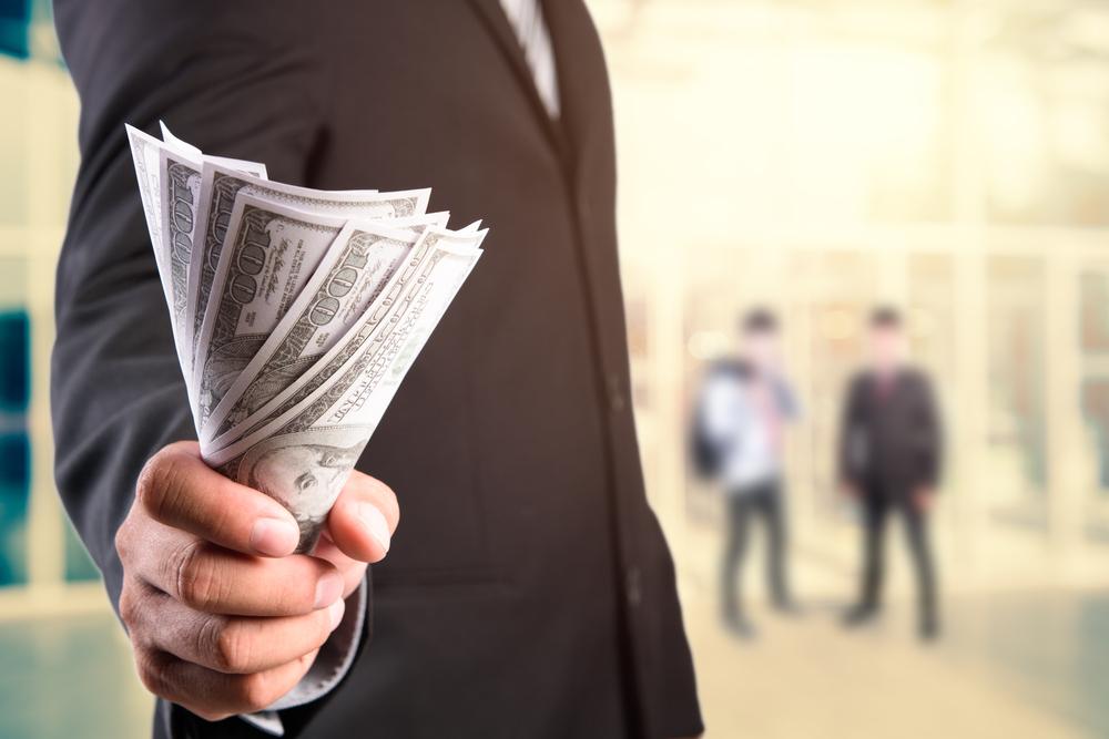 紙幣を握るスーツを着た男性
