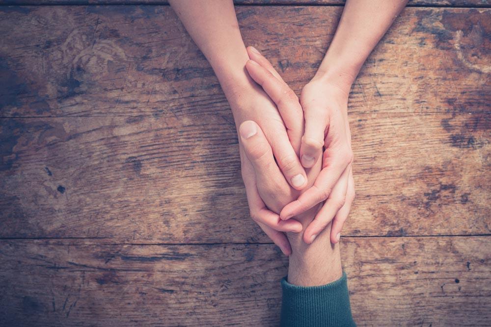 悩む男性の手をそっと握る女性