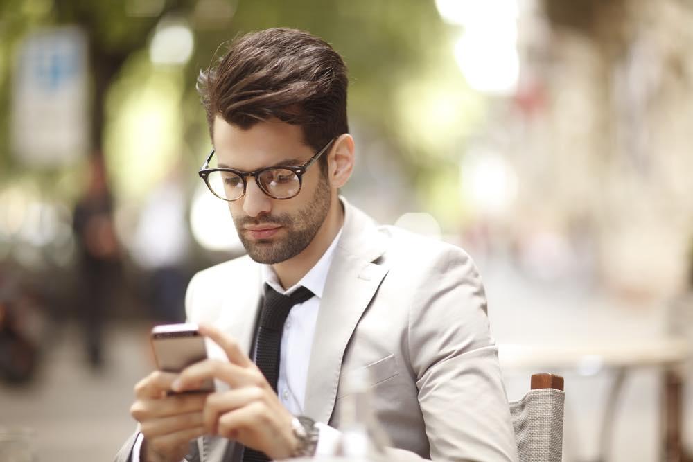 スマートフォンを見る眼鏡をかけてスーツを着た男性