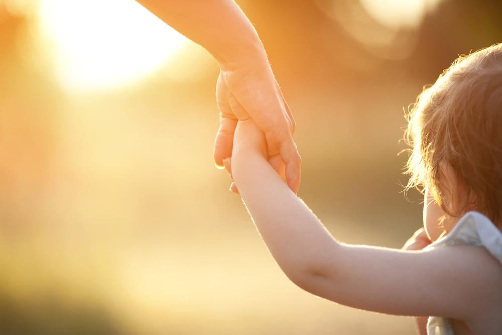 赤ちゃんと手を繋ぐ女性