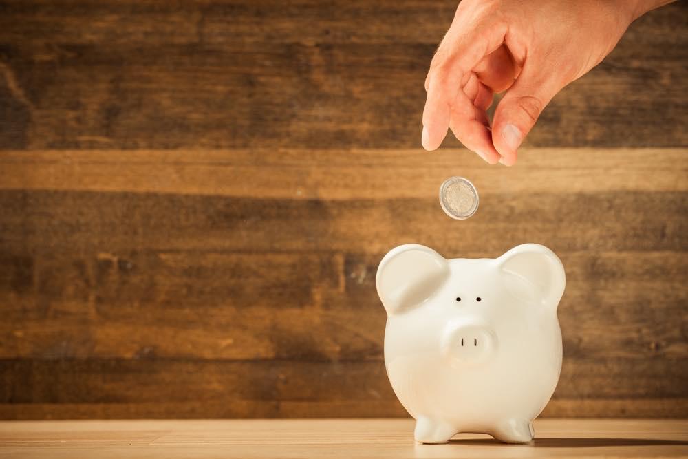 豚の貯金箱にコインを入れる人