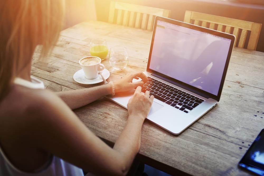 座ってノートパソコンを操作する女性