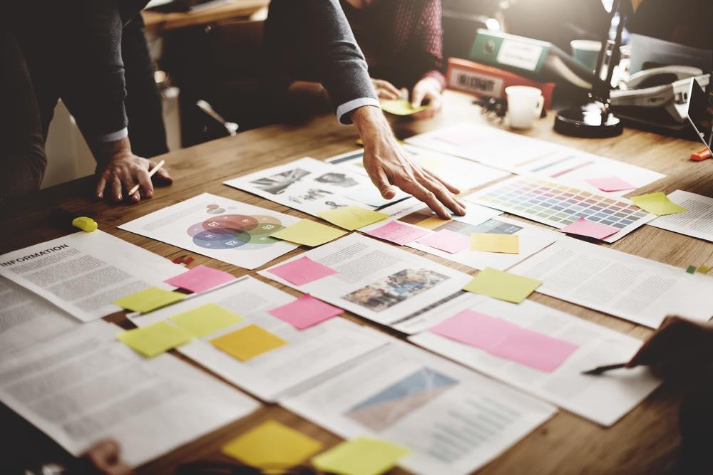 付箋や書類をたくさん机に並べて会議する人々