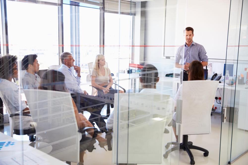 明るい会議室でプレゼンする男性