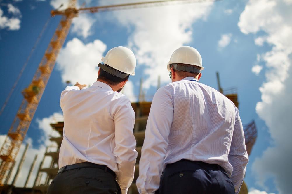 建設現場で話をする安全帽をかぶったビジネスマン