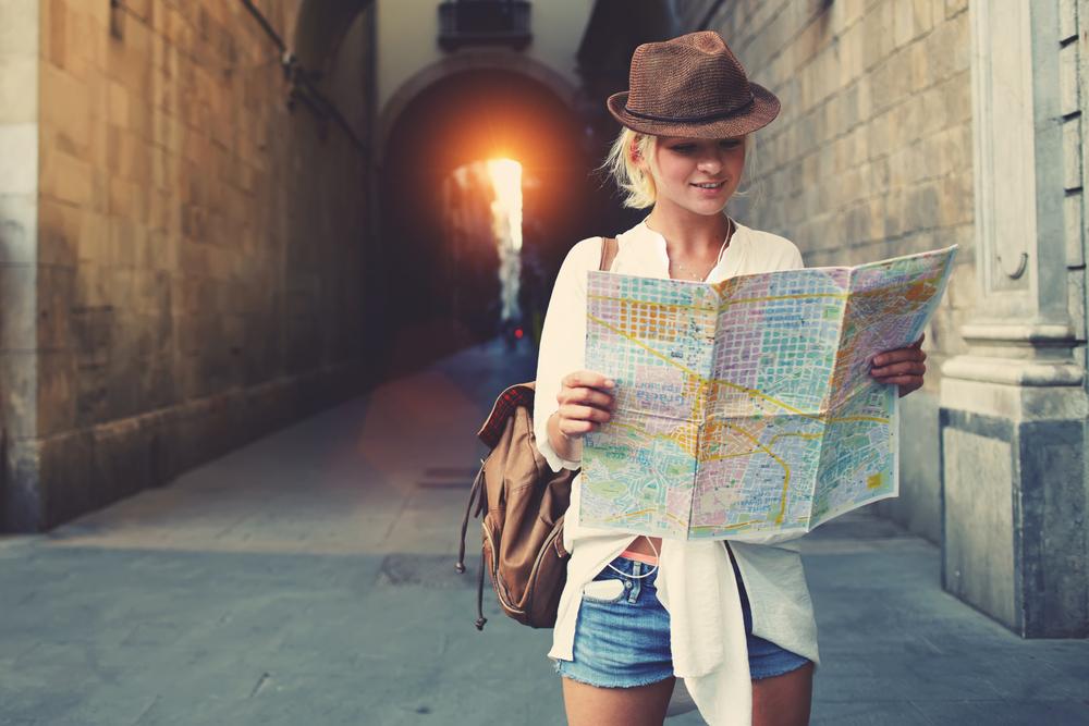 地図を手に見知らぬ道を歩く女性