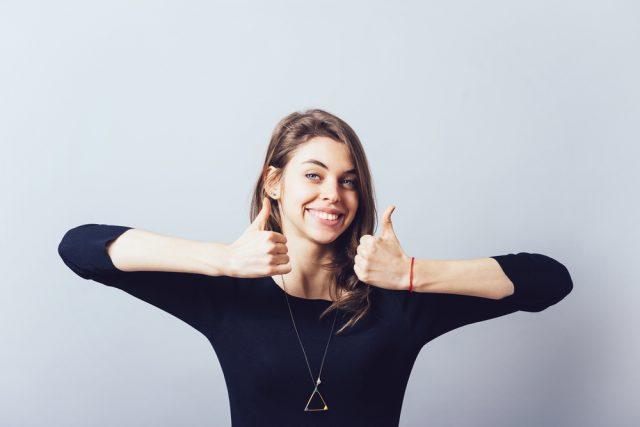 笑顔で「Good」のジェスチャーをする女性