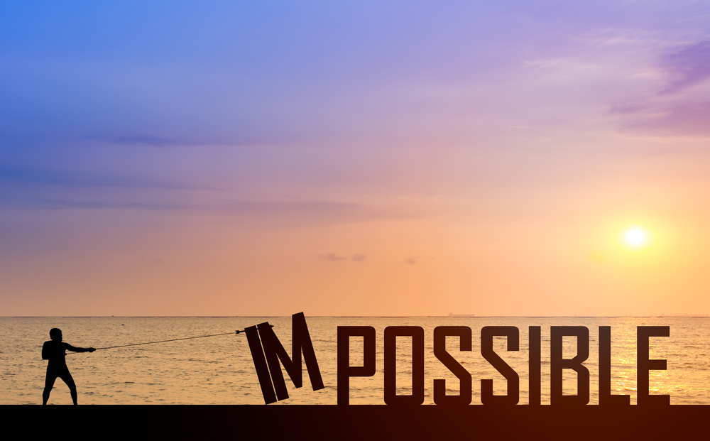 「IMPOSSIBLE」の「IM」を引っ張って取ろうとしている男性のシルエット