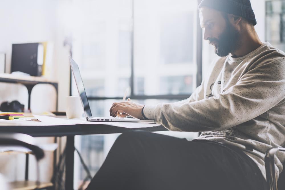 ノートパソコンを使って仕事をする若い男性