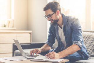 ノートパソコンを使いながら勉強する男性