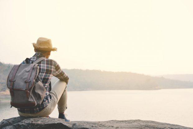 海を眺めるバックパックを背負った男性