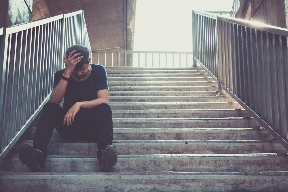 薄暗い階段に座り込み頭を抱える男性