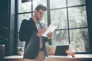 真剣な表情でタブレット端末を操作するジャケットを着た男性