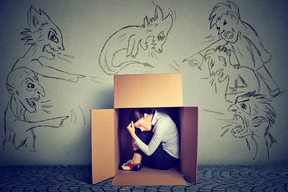 箱に閉じこもる女性と、その女性を叱責する人々のイラスト
