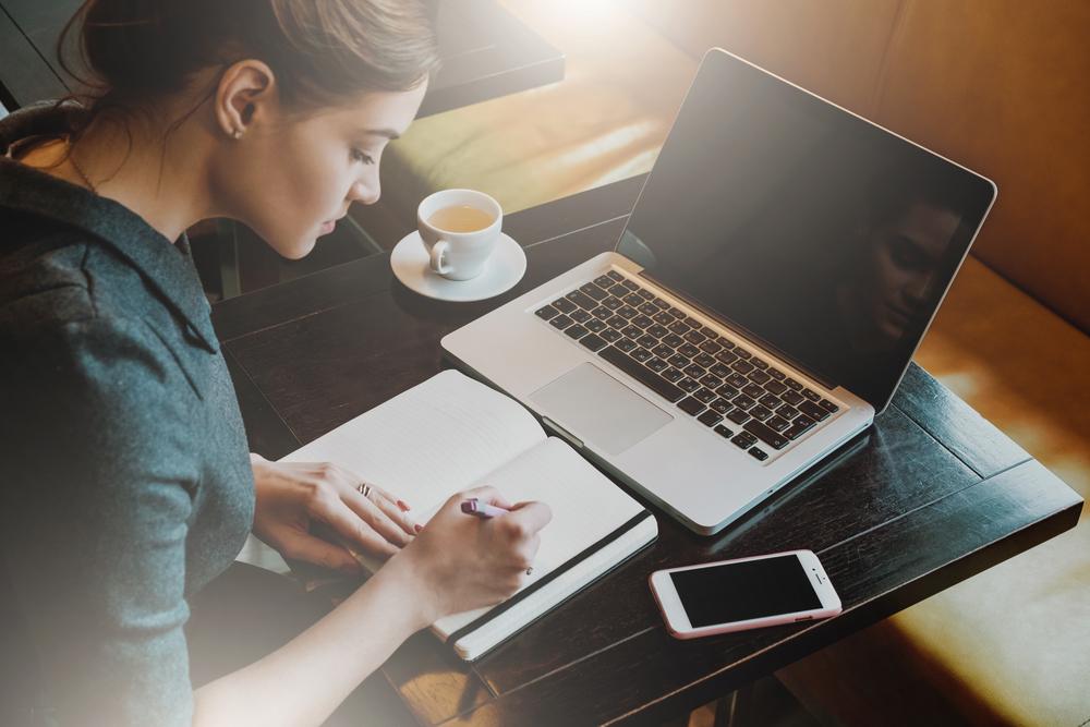 ノートパソコンやスマートフォンを置きながら勉強する女性