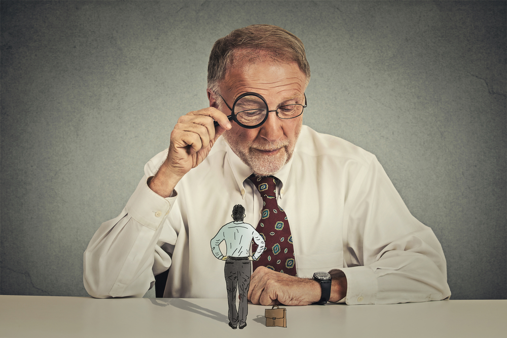 虫眼鏡を使って就活生をよくみようとする面接官
