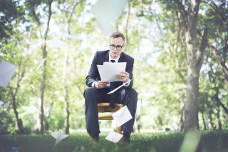 林の中に座り書類を見るスーツの男性