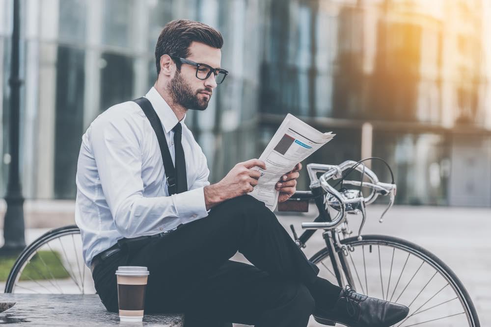 自転車で通勤中にベンチに腰掛け新聞を読む男性