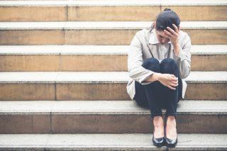 屋外の階段に座り絶望したように頭を抱える女性