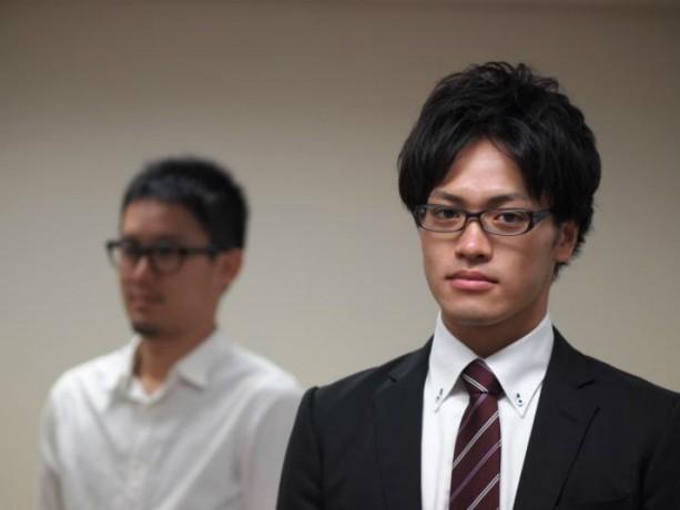 黒縁メガネをかけてスーツを着た若い男性達