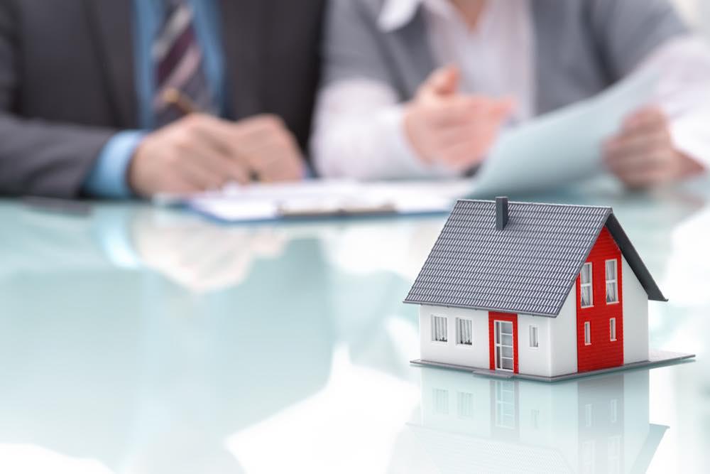営業する男女と家の模型