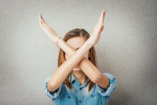 手で大きくバツを作っている女性