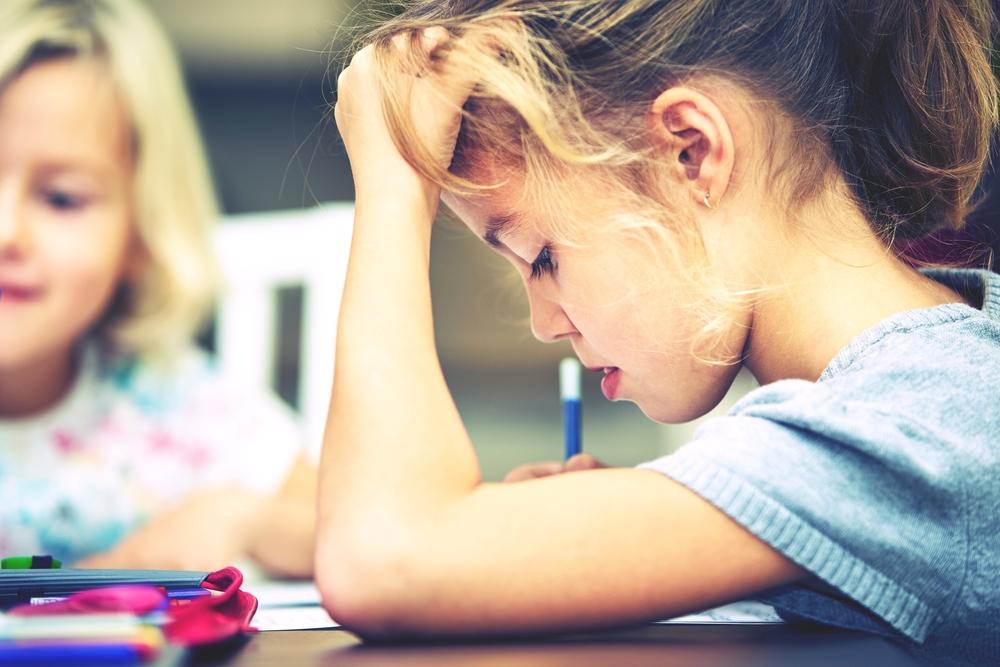 勉強中に悩んで頭をかく少女