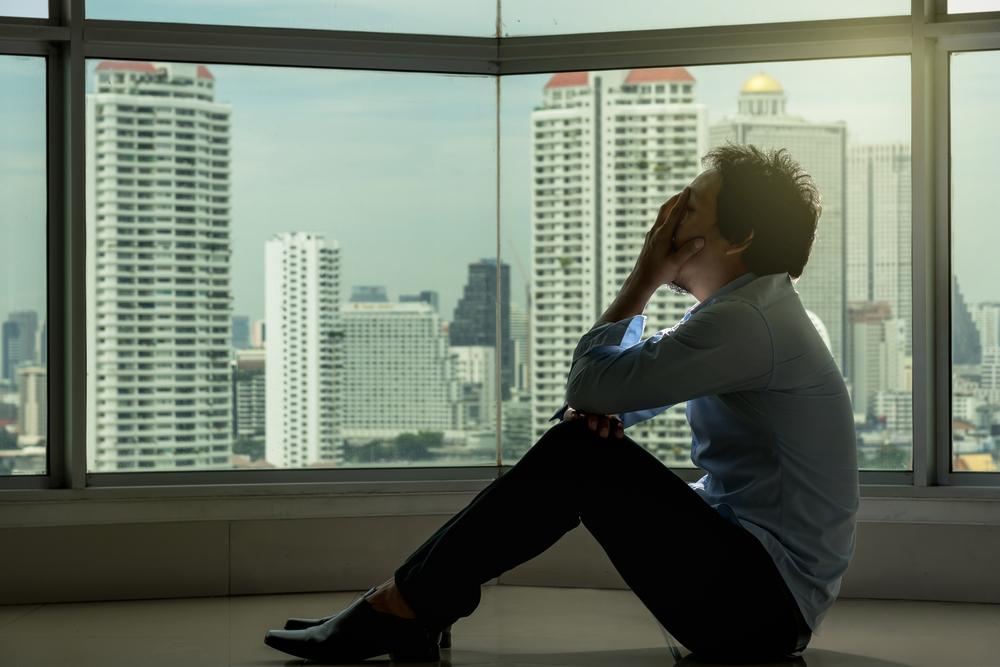窓際の床に座り込み顔を覆って絶望する男性