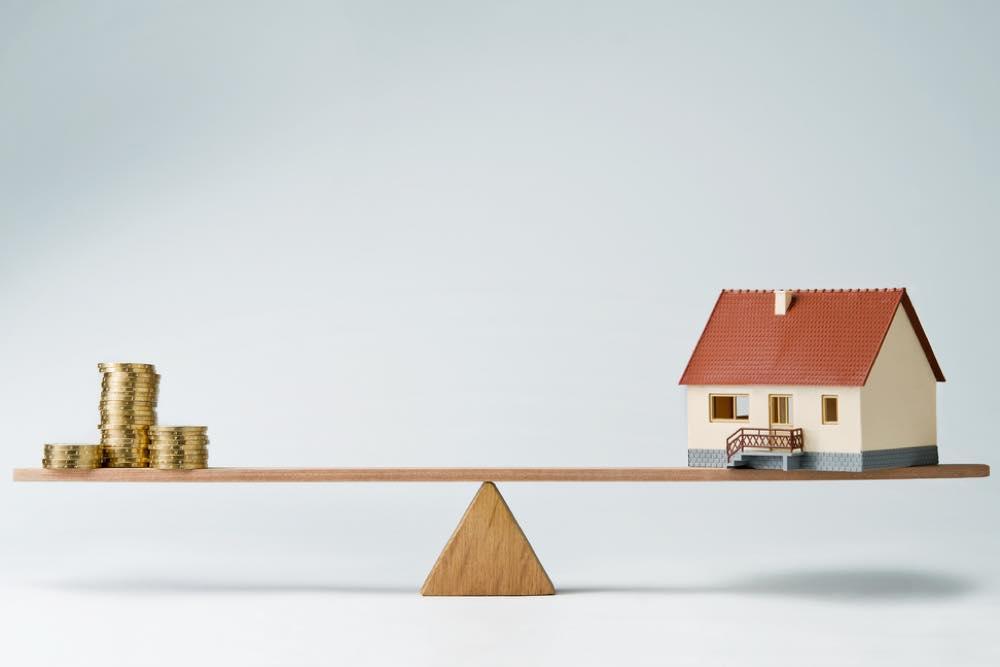 シーソーの上に乗ったコインと家の模型