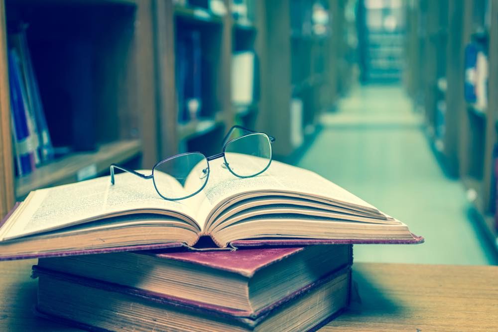 重ねて置かれた古い本とメガネ