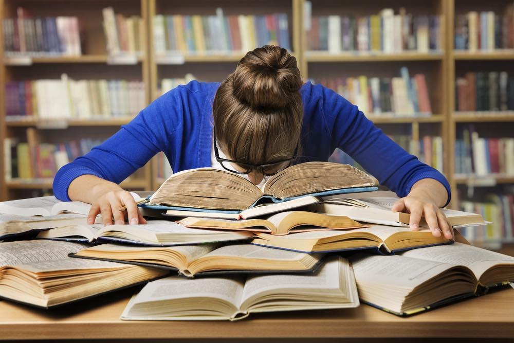 たくさんの本の山に突っ伏する勉強中の女性