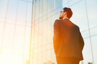 朝日を受けながらビルの前に立つスーツを着た男性
