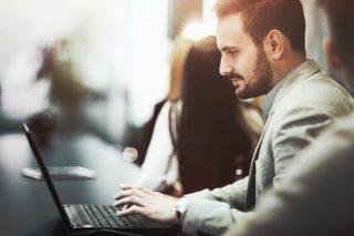 ノートパソコンを開いて仕事をする男性