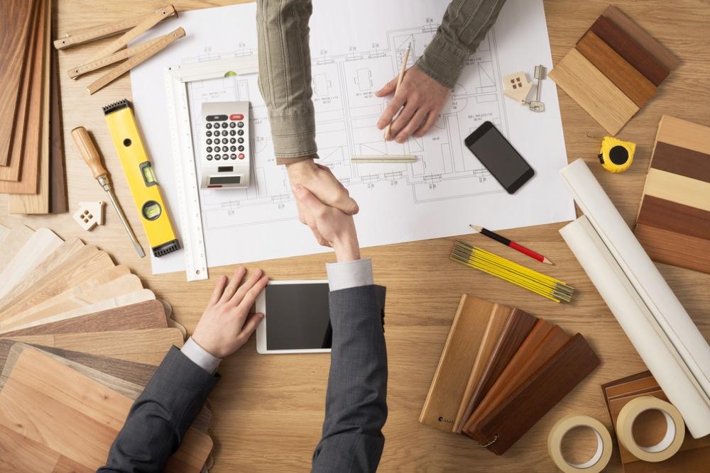 設計図を書きながら客と握手をする男性