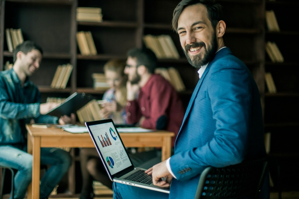 笑顔で振り返る青色のスーツを着た男性