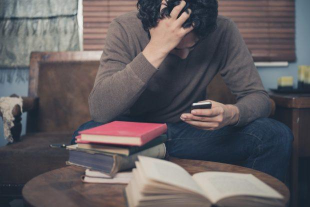 頭を抱えてスマートフォンを見る男性