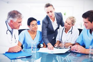 医療関係者に書類を使って説明をする、グレーのスーツを着た女性