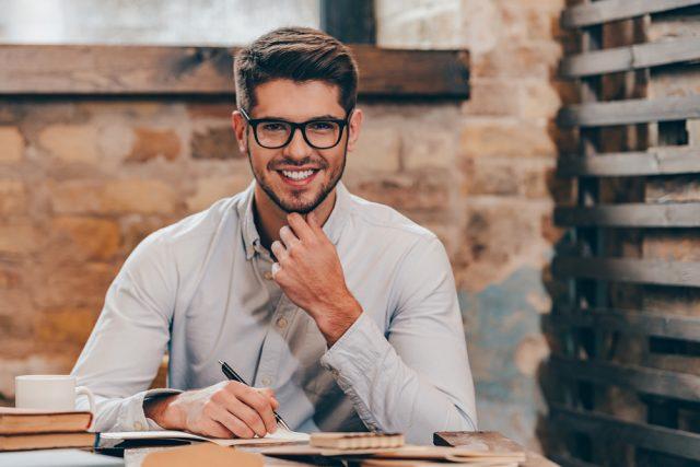 勉強をするメガネをかけた笑顔の男性