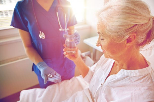 高齢の女性に薬と水を渡す看護師