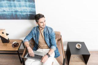 室内でソファーに座りながらノートパソコンを使う男性