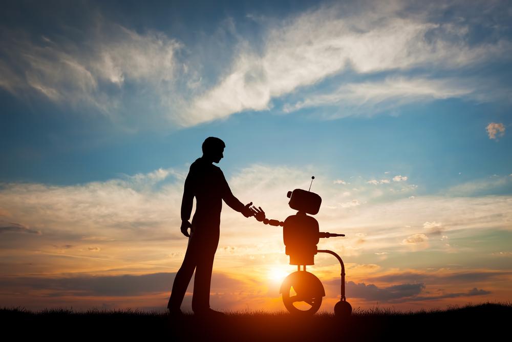 夕日を背景にロボットと握手をする人