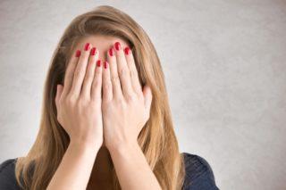 両手で顔を隠す赤いマニキュアをつけた女性