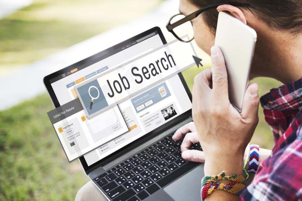 ノートパソコンを開いてインターネットで仕事を探す人
