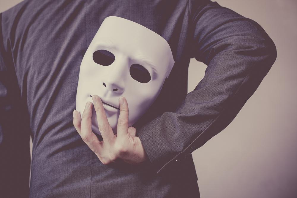 後ろ手に仮面を隠し持つスーツ姿の男性
