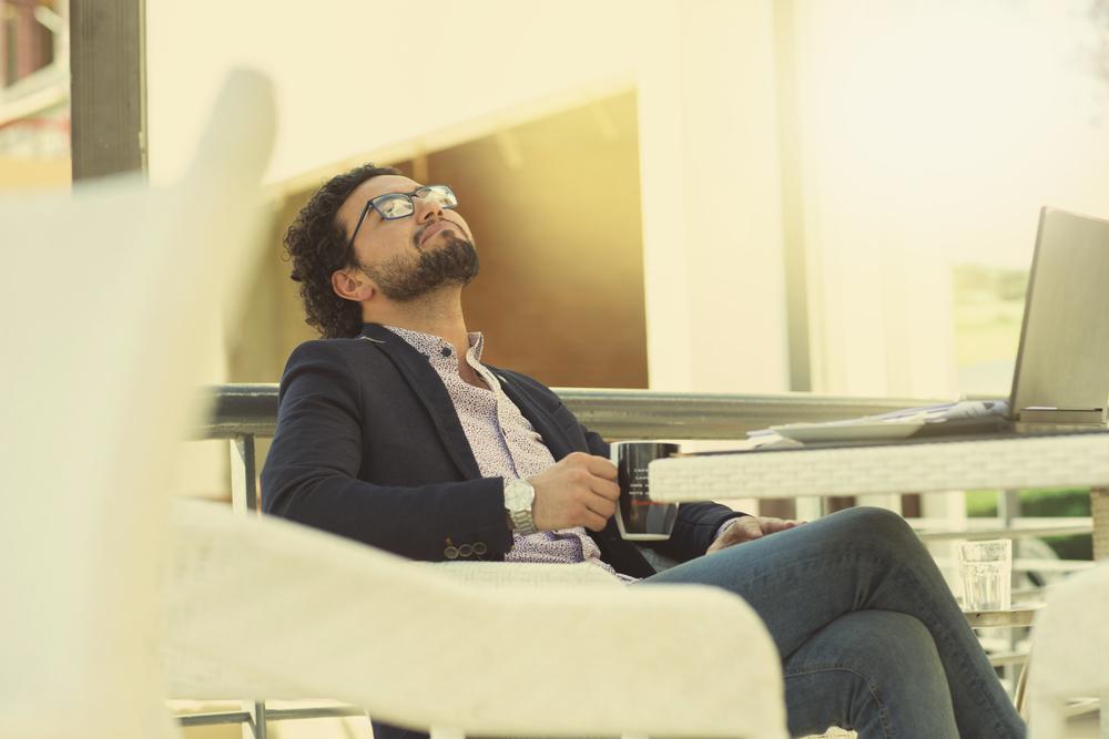 ソファーに座ってリラックスしながら考え事をする男性