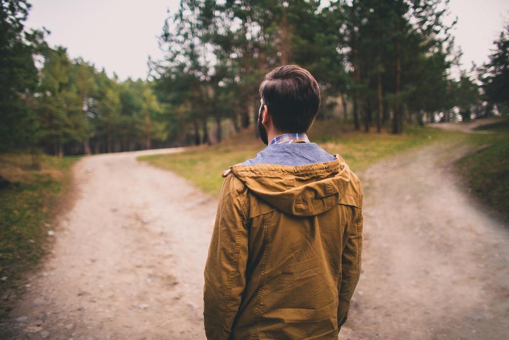 行き先が二つに分かれた道に立つ男性