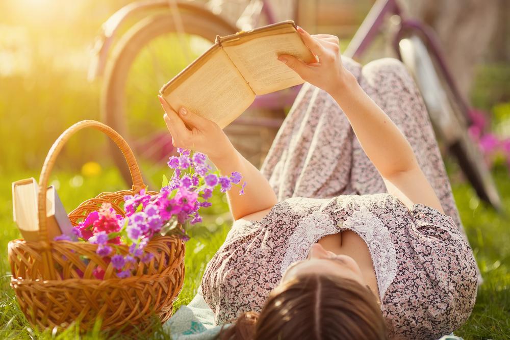 芝生の上に寝転びながら本を読むワンピースを着た女性